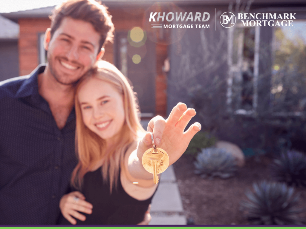 Happy married couple standing outdoors in front of new home holding keys